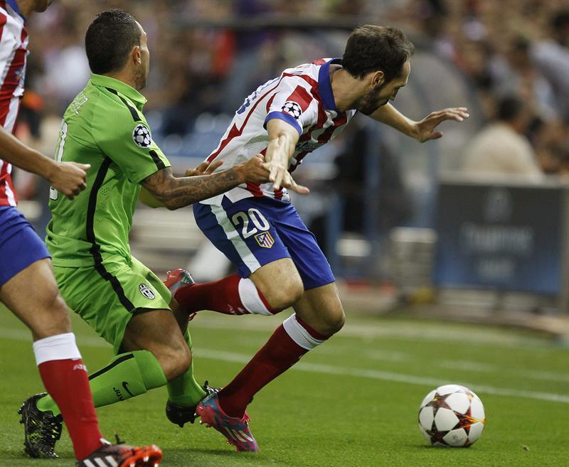 El defensa del Atlético de Madrid Juanfran (d) lucha el balón con el argentino Carlos Tévez, de la Juventus. Foto: EFE