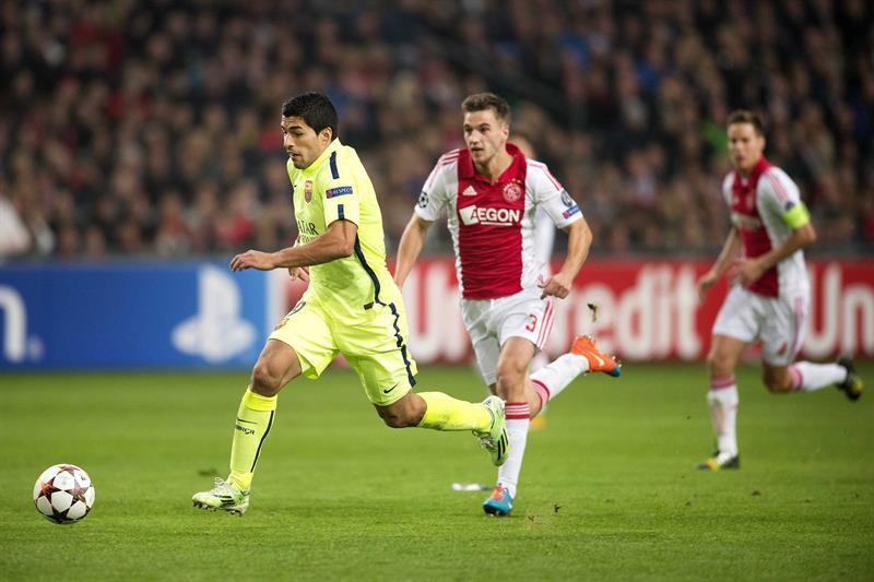 Luis Suárez (i), delantero uruguayo del FC Barcelona, controla el balón ante Joel Veltman (c), del Ajax de Ámsterdam. Foto: EFE