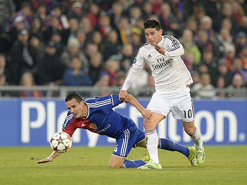 James Rodríguez (d), del Real Madrid, pelea por el balón con Philipp Degen. Foto: EFE