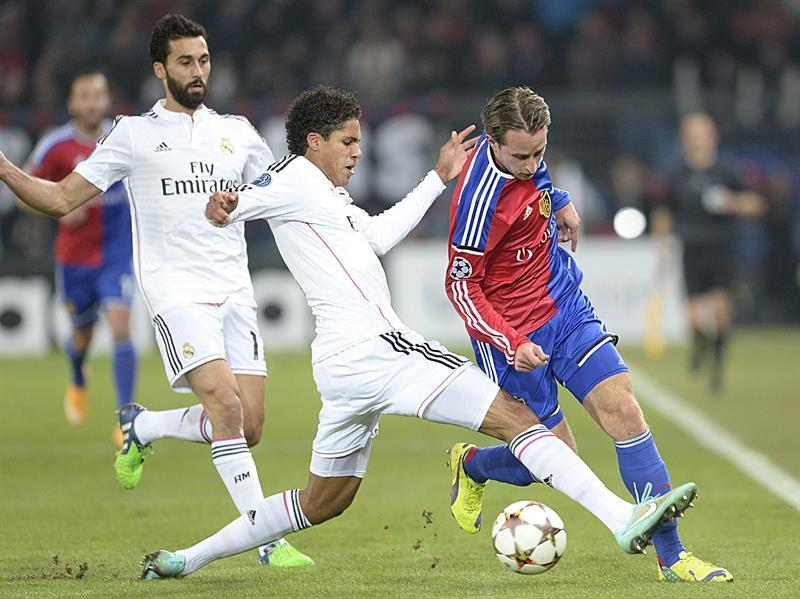 Raphael Varane (c) y Álvaro Arbeloa (i), del Real Madrid, pelean por el balón. Foto: EFE