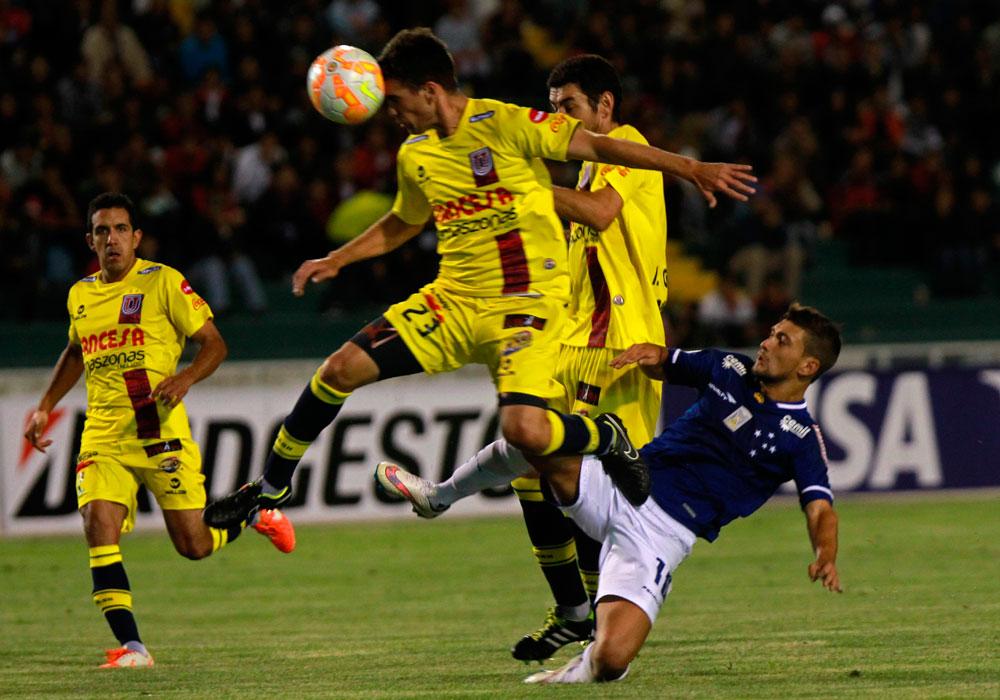 El jugador de Universitario Nicolás Filippetto (i) cabecea el balón ante la marca de De Arrascaeta (d), de Cruzeiro. Foto: EFE