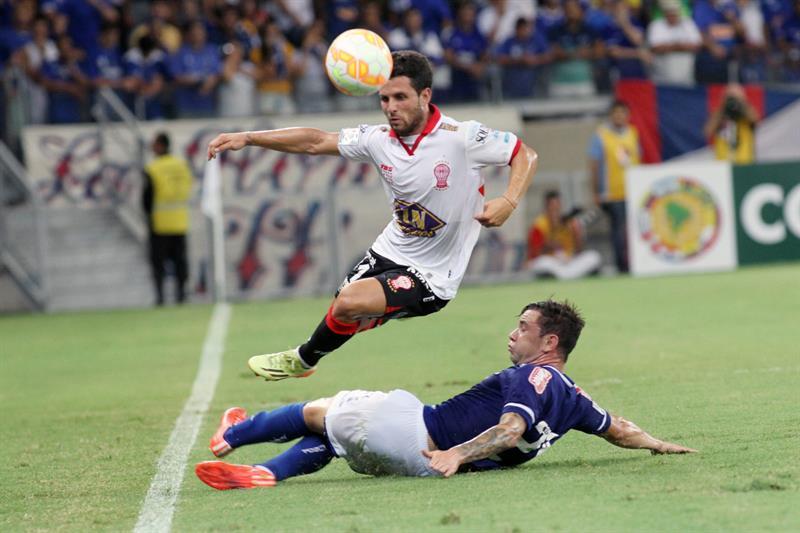 Eugenio Mena (abajo) de Cruzeiro disputa el balón con Agustín Torassa (arriba) de Huracán. Foto: EFE