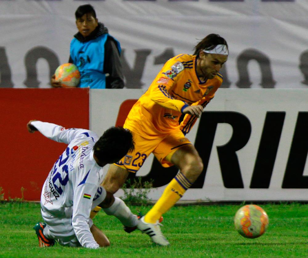 El jugador Edgar Lugo (d) de Tigres de México en acción ante la marca Ricardo Verduguez de San José. Foto: EFE