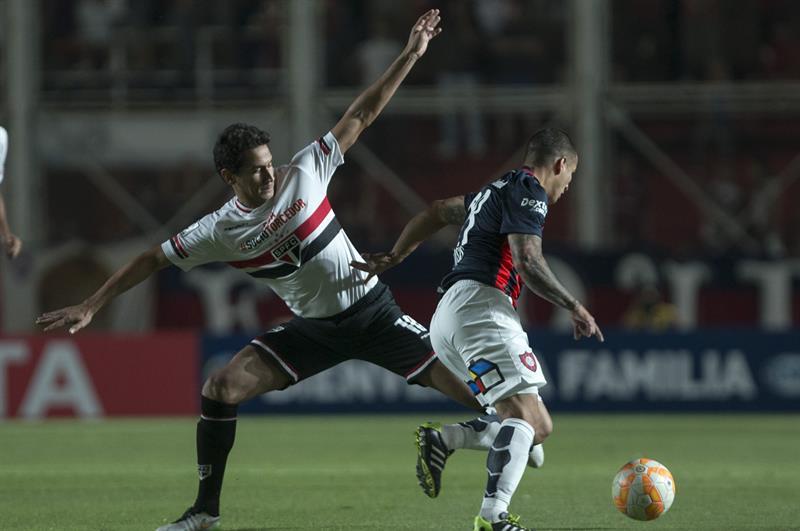El jugador Franco Mussis (d) de San Lorenzo de Argentina disputa el balón con Ganso de San Pablo de Brasil. Foto: EFE