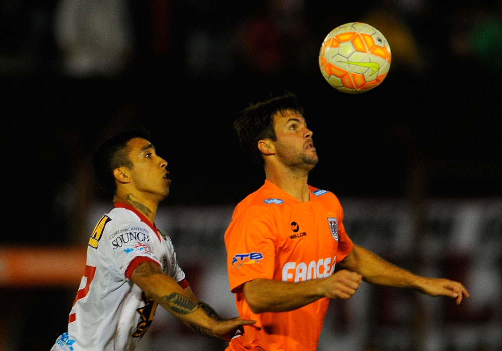 Edson Puchi (i) de Huracán sale a la marca de Federico Silvestre (d) de Universitario. Foto: EFE