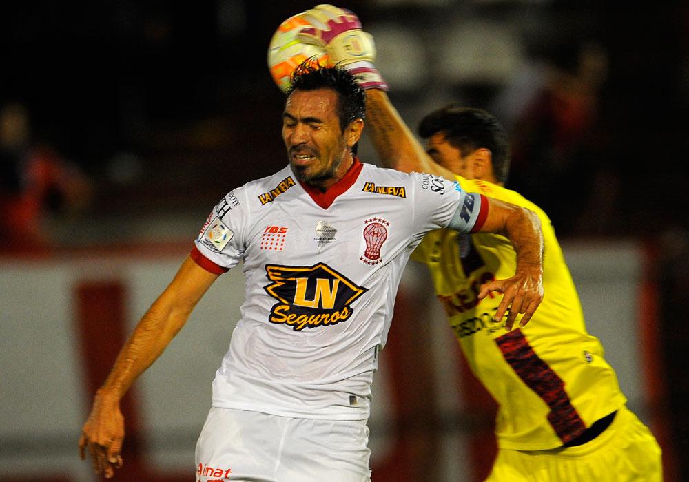 Eduardo Domínguez (i) de Huracán enfrenta al portero  Raúl Olivares (d) de Universitario. Foto: EFE