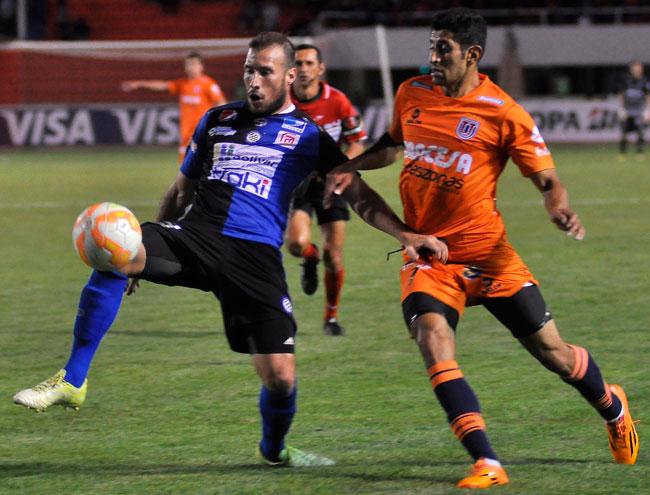 El jugador de Universitario David Castro (d) disputa el balón con José Velásquez (i) de Mineros. Foto: EFE