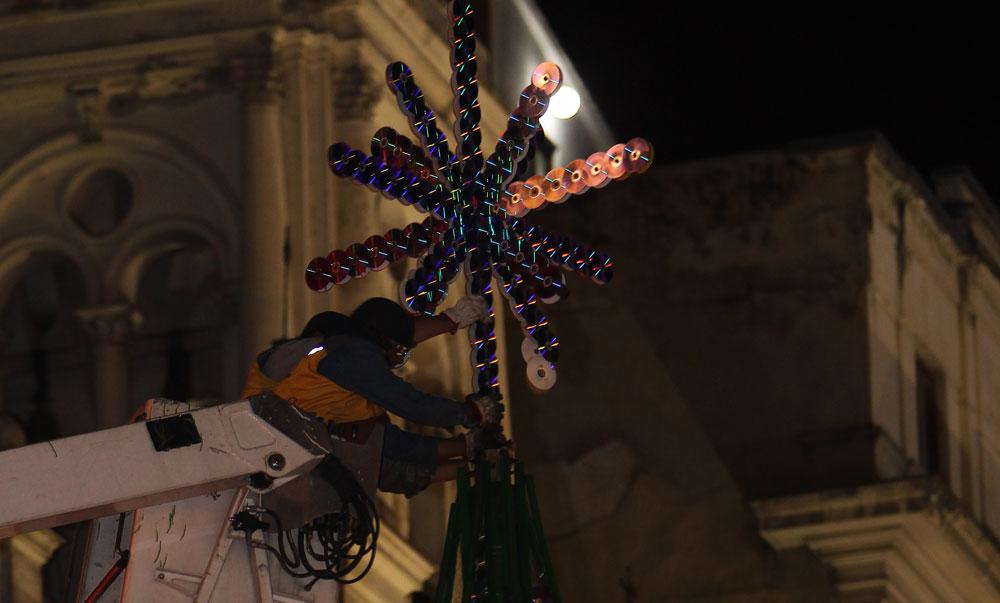 Un trabajador municipal coloca la estrella que corona el árbol hecho con discos compactos en desuso. Foto: EFE