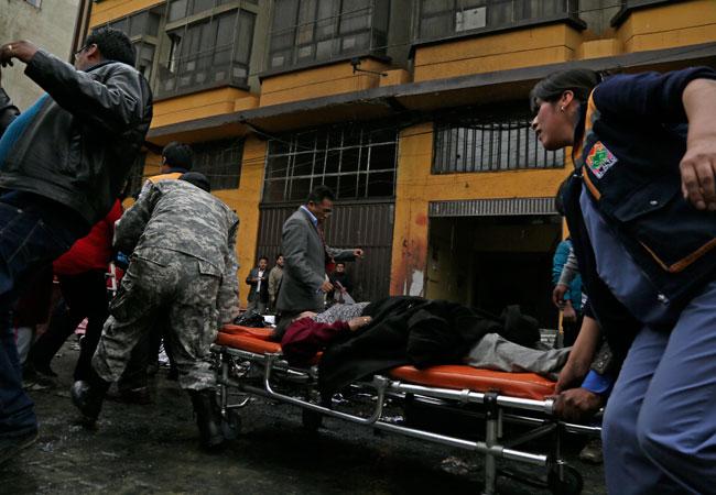 Autoridades y rescatistas transportan a un herido a causa del incendio en oficinas de la alcaldía de El Alto. EFE