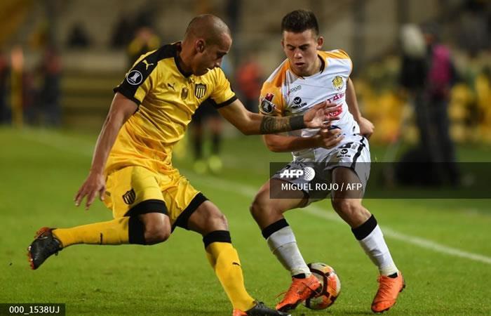 El uruguayo de Peñarol Guzmán Pereira (L) compite por el balón con el boliviano Henry Vaca de The Strongent. Foto: AFP