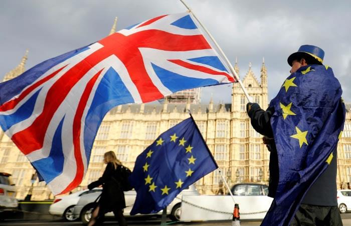 Un hombre contrario al Brexit se manifiesta frente al Parlamento cubierto por una bandera europea y haciendo ondear una bandera británica. Foto. AFP.