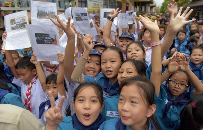 Estudiantes tailandeses sonríen mientras sostienen fotos de los 12 niños y un entrenador de fútbol frente al hospital después de que el grupo fue rescatado. Foto. AFP.