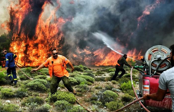 Los bomberos intentan controlar el incendio forestal cerca del pueblo de Kineta, en los suburbios de Atenas. Foto. AFP.