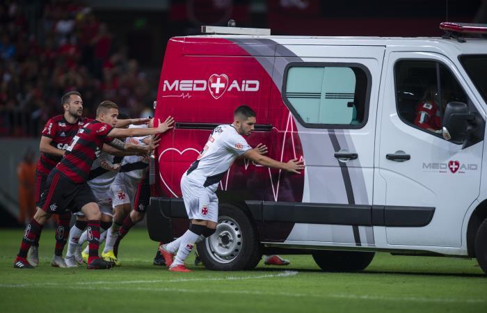 Jugadores de Flamengo y Vasco da Gama empujan la ambulancia fuera del campo de juego. Foto: AFP