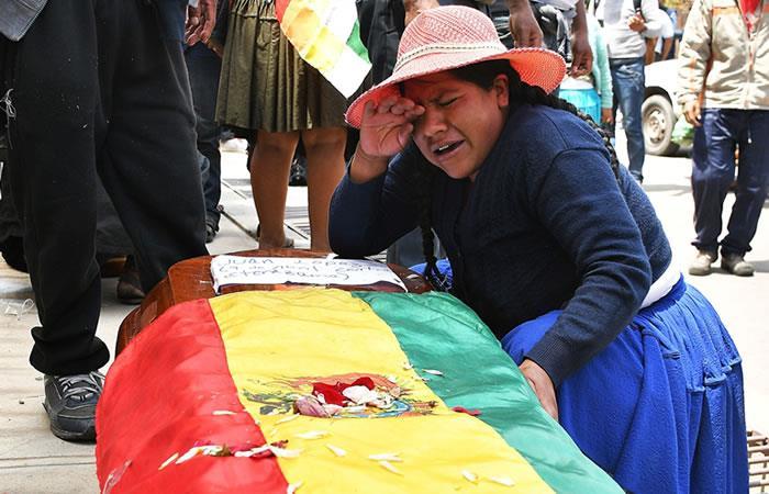 Mujer llora sobre el féretro de uno de los fallecidos. Foto: EFE