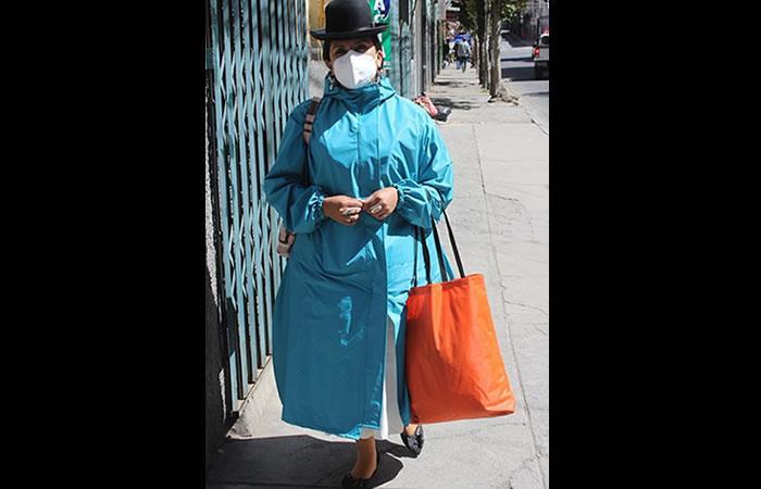 Mónica Calizaya hace la demostración en la calle del uso de un traje de bioseguridad. Foto: EFE.