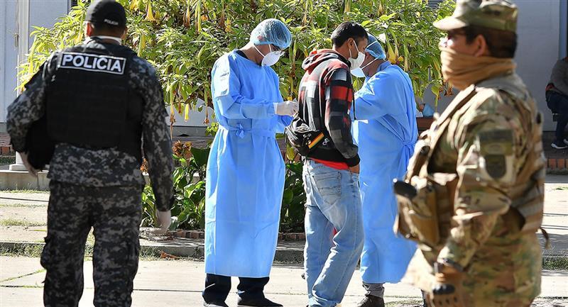 Policías y funcionarios de salud realizan las medidas de prevención en Cochabamba . Foto: EFE