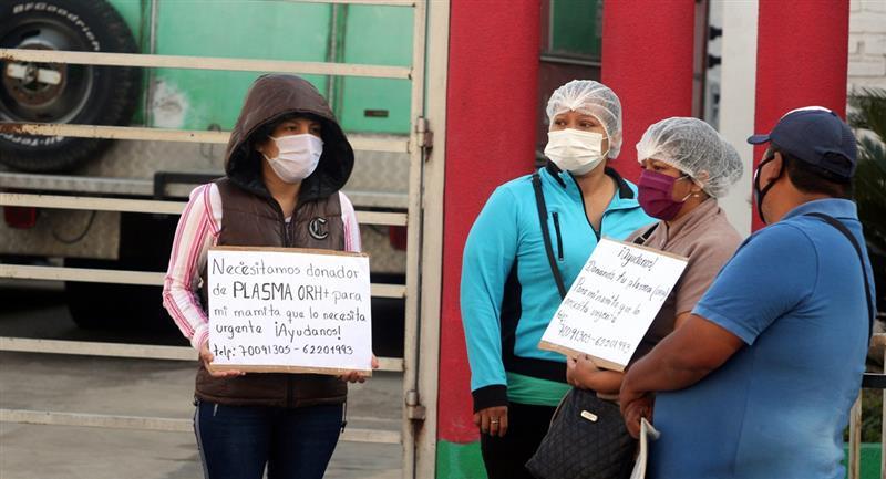 Familiares de enfermos de coronavirus buscan un donante cerca del Banco de Sangre de Santa Cruz. Foto: EFE