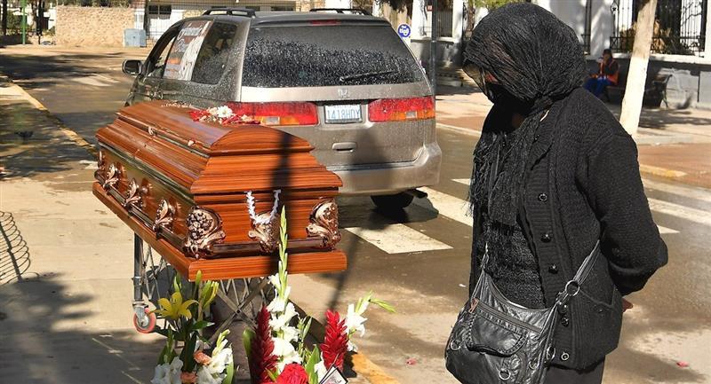 Una mujer espera junto a un féretro afuera del cementerio. Foto: EFE