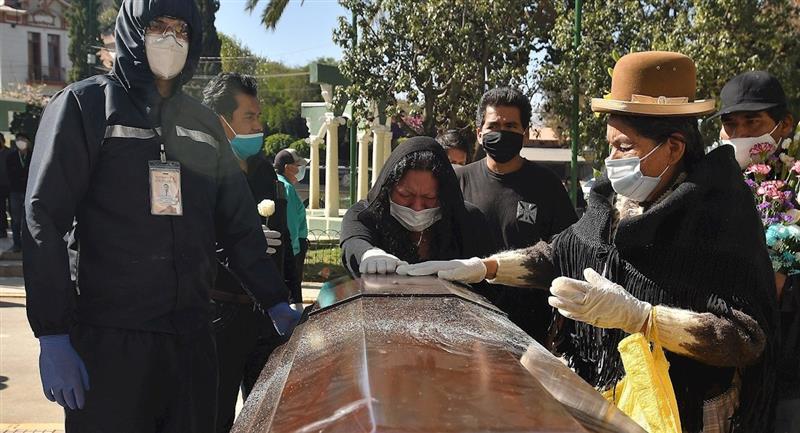 Familiares despiden a un ataúd a las puertas del cementerio. Foto: EFE