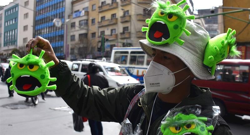 El paceño Miguel Huallpara muestra los títeres de coronavirus a sus clientes. Foto: EFE
