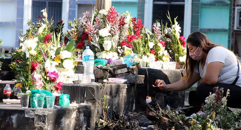 Una mujer realiza una ofrenda conocida como 'Cruz de las almas olvidadas' en el cementerio Sagrado Corazón de Jesús. Foto: EFE