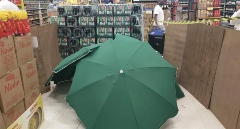 Los empleados del supermercado cubrieron el cuerpo con varias sombrillas. Foto: Twitter @ErreVillegas