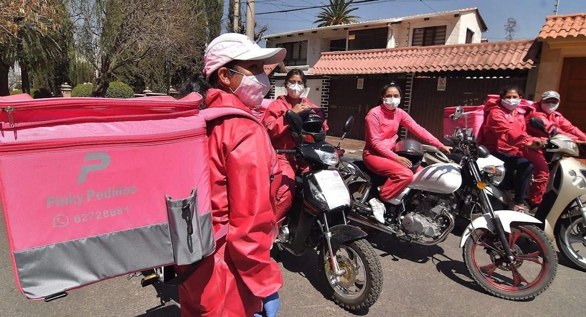 """Las trabajadores de """"Pink Delivery"""" salen a realizar entregas con trajes de bioseguridad color rosa. Foto: EFE"""