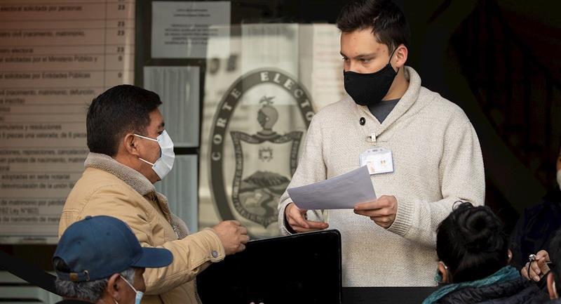 Personas hacen fila para justificar su inasistencia en las elecciones. Foto: EFE