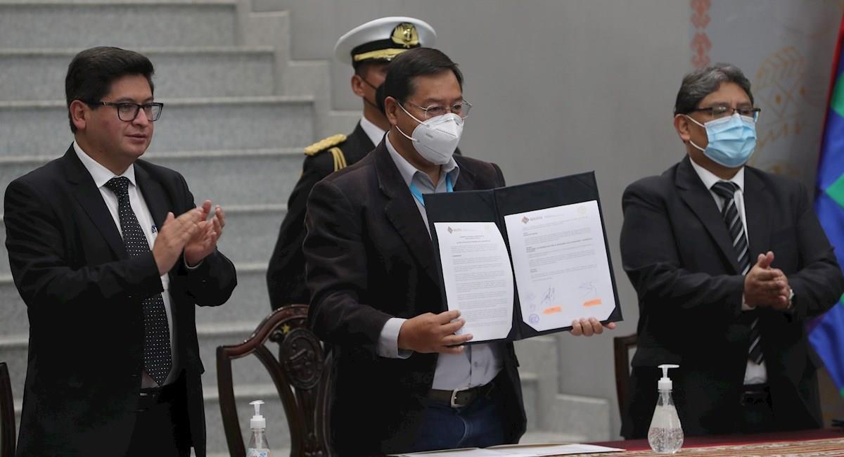 Luis Arce muestra la firma del Programa Fiscal Financiero 2021. Foto: EFE