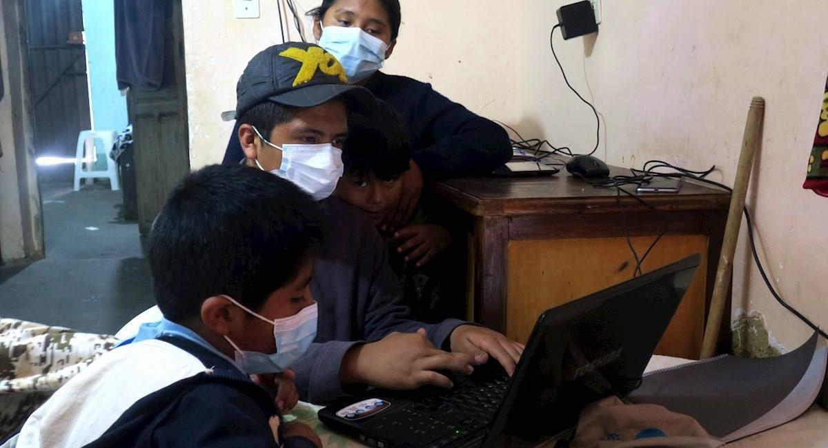 Noemí Andrade y sus hijos utilizan el computador. Foto: EFE
