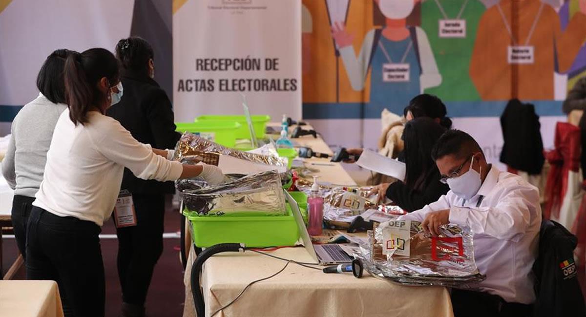Personas trabajan en el conteo de las actas de votación en el centro de computo del TED. Foto: EFE