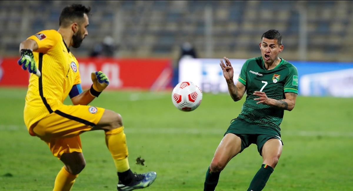 El arquero Claudio Bravo disputa el balón con Juan Carlos Arce. Foto: EFE