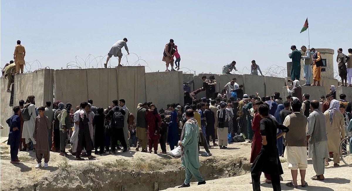 Afganos se agolpan a lo largo del muro del aeropuerto internacional Hamid Karzai. Foto: EFE